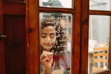 Young woman writing on glass of shop