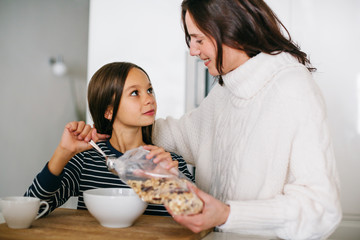 Mother and her daughter preparing healthy breakfast in the kitchen.