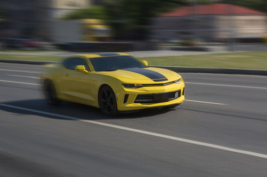 Yellow sports car racing down the city street