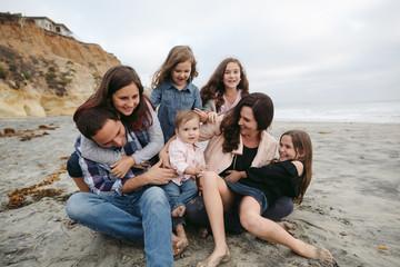 Family wrestling on beach having fun