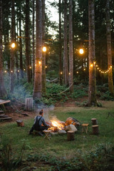 a man tends a campfire in the forest