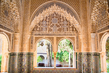 Moorish architecture in one room of the Nasrid Palaces of the Alhambra of Granada in Spain, with beautiful intricate carvings and windows overlooking a garden.