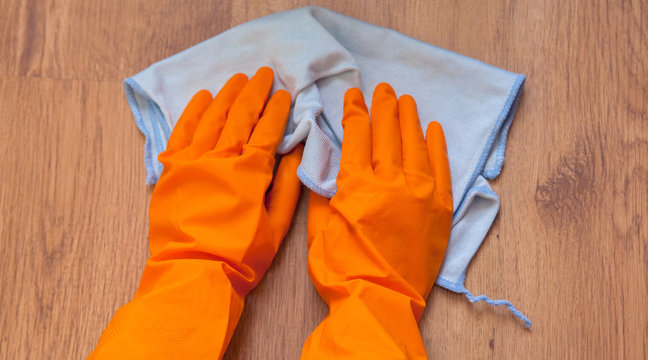 A woman hands Using blue rags wipe the wooden floor