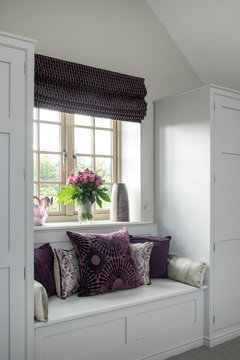 Integrated bedroom storage units around a window with matching cushions and flowers.
