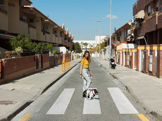 Fashionable model walking with dog on street