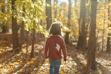 Cute young girl in a sweater walking in the woods
