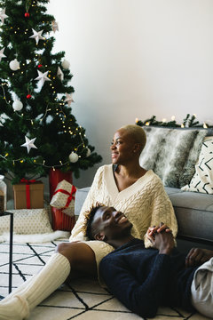 Young multiethnic couple relaxed at home on Christmas.