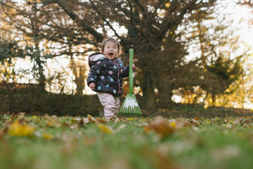 Excited baby with rake outdoors