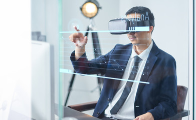 Asian businessman wearing virtual reality goggle and pointing business growth chart in a office .