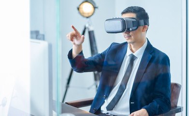 Asian businessman wearing virtual reality goggle and pointing up in a office .