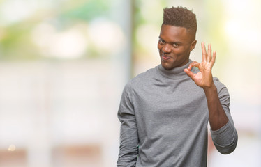 Young african american man over isolated background smiling positive doing ok sign with hand and fingers. Successful expression. Fototapete