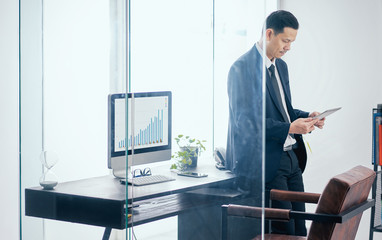 Asian businessman in the office standing and using a digital tablet to work .