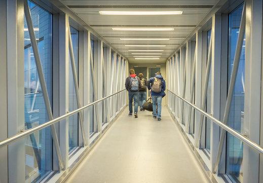 Passengers goes to airplane through jet bridge