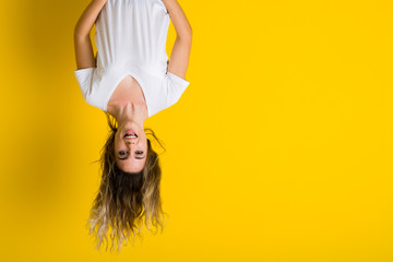 Beautiful young blonde woman jumping happy and excited hanging upside down over isolated yellow background Wall mural