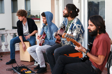 young people playing music together on a terrrace on a rooftop at sunset