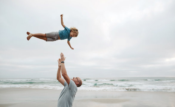 Dad throwing kid up in the air at the beach