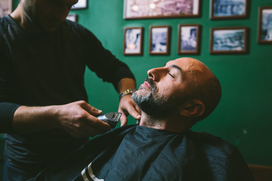 The man is shaved in a barber shop