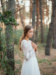 Sensual model in gentle dress in woods
