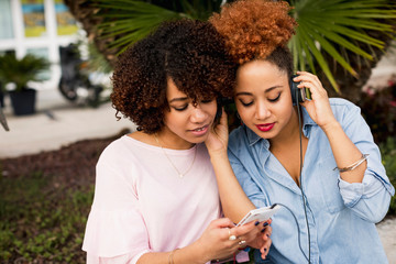 Two female friends listening music outdoor