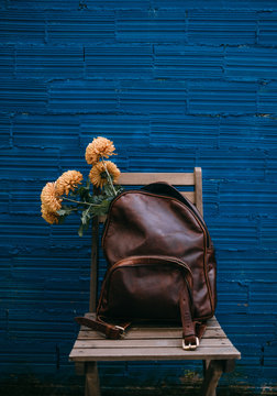 flowers inside a leather backpack on a wooden chair in front of a blue wall