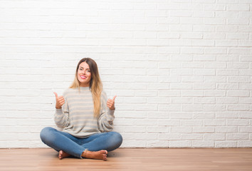 Young adult woman sitting on the floor over white brick wall at home success sign doing positive gesture with hand, thumbs up smiling and happy. Looking at the camera with cheerful expression Wall mural