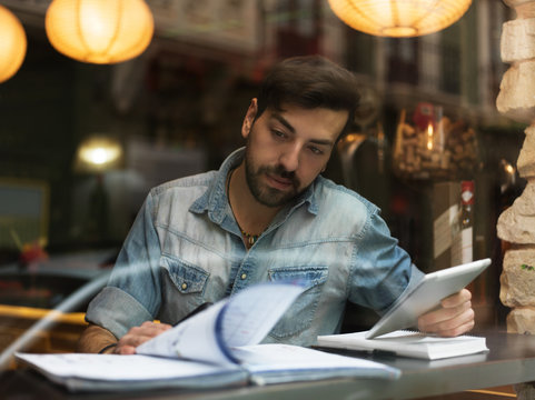 Concentrated man working with papers in bar