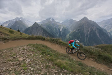 Woman riding mtb downhill singletrack in mountains on a rainy day