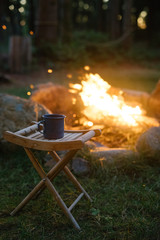 a campfire with an enamel cup on a wooden stool