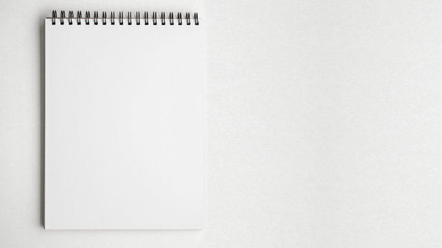 Blank pape notepad on white table background.