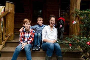 three kids and their dog posing for christmas photos