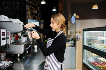 Concentrated pretty barista making coffee