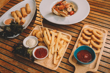 onion rings, french fries, chicken nuggets, Spring rolls, spaghetti pasta with shrimps over wooden table