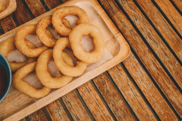 fast food products : onion rings and ketchup on the wood plate over wooden table