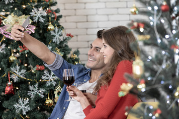 Young good looking Caucacian couple taking picture by man cellphone and drinking red wine in Christmas time.