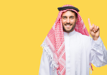 Young handsome man wearing keffiyeh over isolated background showing and pointing up with finger number one while smiling confident and happy.
