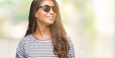 Young beautiful arab woman wearing sunglasses over isolated background looking away to side with smile on face, natural expression. Laughing confident.