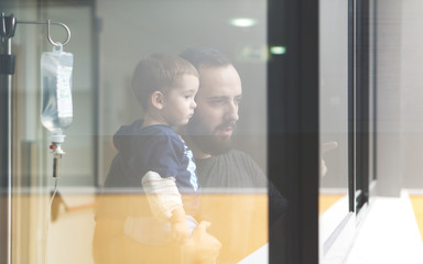 Father holding his son in arms looking through the window