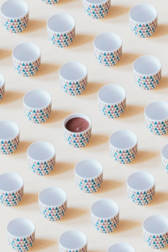 Pattern of empty mugs with just one mug with chocolate
