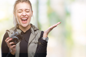Young blonde woman taking pictures using vintage camera over isolated background very happy and excited, winner expression celebrating victory screaming with big smile and raised hands