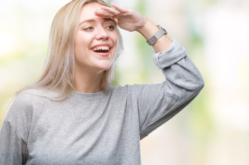 Young blonde woman over isolated background very happy and smiling looking far away with hand over head. Searching concept.