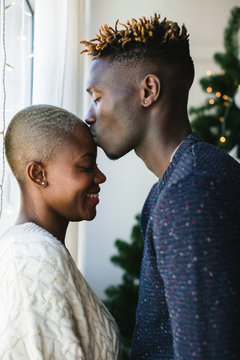 Young multiethnic couple kissing at home on Christmas.