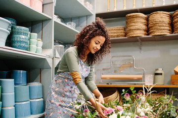 Young model with flowers working in shop