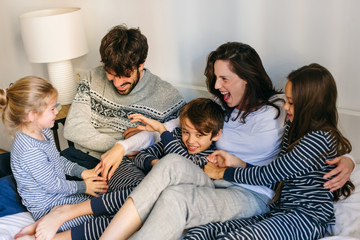 Happy family wearing pajama on bed.