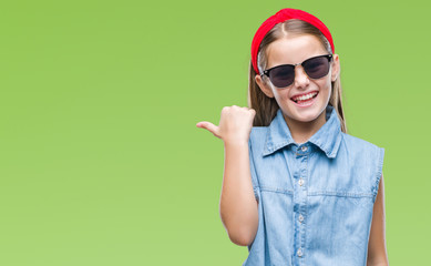 Young beautiful girl wearing sunglasses over isolated background smiling with happy face looking and pointing to the side with thumb up.