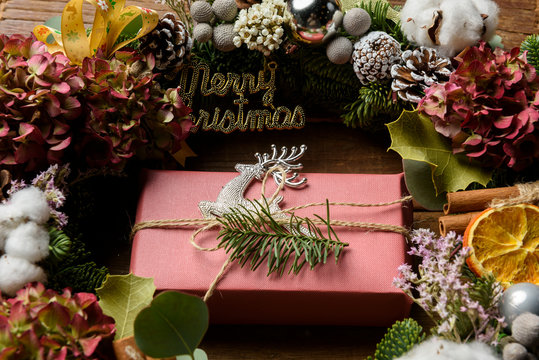 Wreath, gift box and pine cone on white wood for Christmas decor