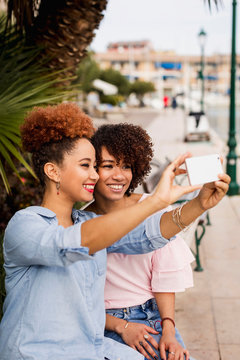 Two female friends using mobile phone and having fun
