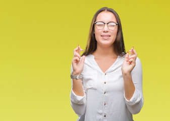 Young caucasian beautiful business woman wearing glasses over isolated background smiling crossing fingers with hope and eyes closed. Luck and superstitious concept.