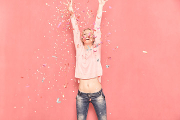 one young woman happy with arms outstreched high in air with confetti thrown, 20-29 years old, long blond hair. Shot in studio on pink background.