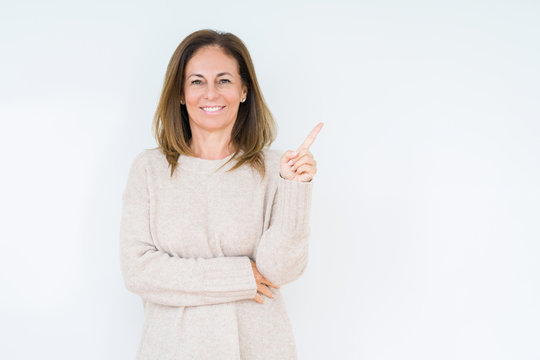 Beautiful middle age woman over isolated background with a big smile on face, pointing with hand and finger to the side looking at the camera.