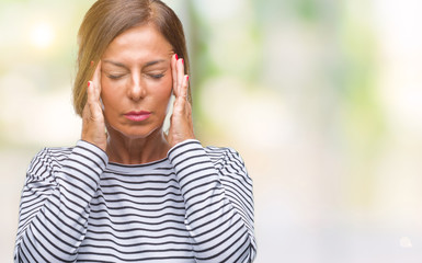 Middle age senior hispanic woman over isolated background with hand on head for pain in head because stress. Suffering migraine.